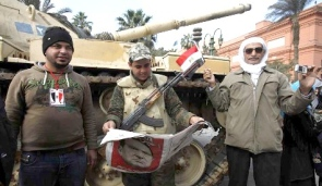 People stand next to a soldier while he reads a newspaper in front of an army tank at Tahrir square in Cairo, February 12, 2011.